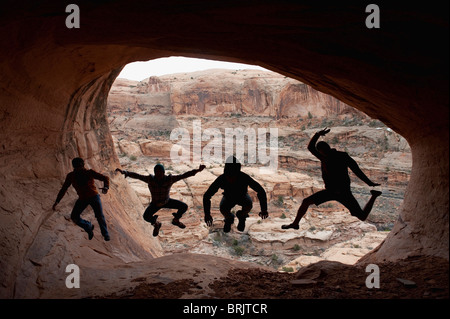 Four young men jumping are silloutted against the mouth of a cave in Moab, UT. - Stock Photo