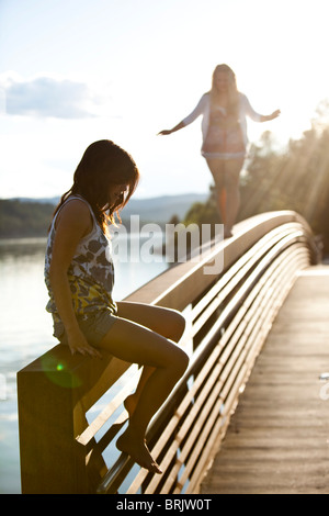 Two young women balance on a metal bridge in Idaho. - Stock Photo