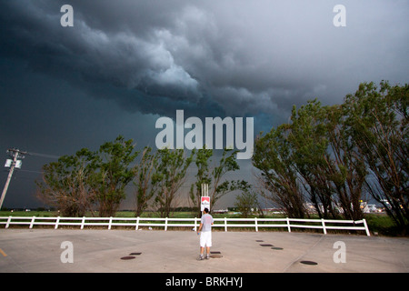 A man stands in a parking lot and watches a squall line descend upon him. May 24, 2010. - Stock Photo