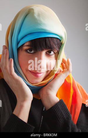 Brunette girl in multicolored head scarf; photographed on gray background - Stock Photo