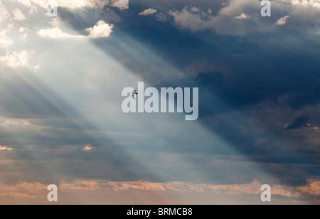 Sun shining through dark clouds - Stock Photo