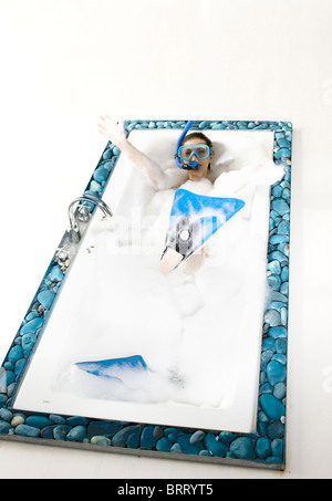 Young woman enjoying the bath-foam in the bathtub with blue rubber scuba tools - Stock Photo