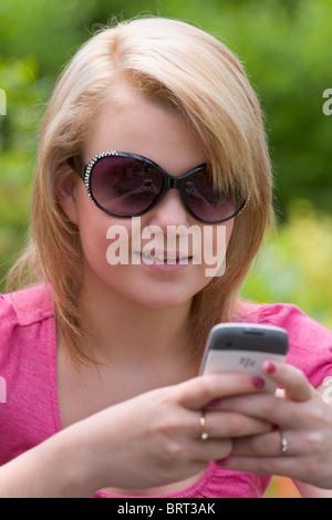 Teenage girl wearing sunglasses texting on a mobile phone, England, - Stockfoto