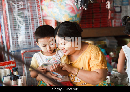 A Burmese woman helps her son to read, Mae sot, Thailand - Stock Photo