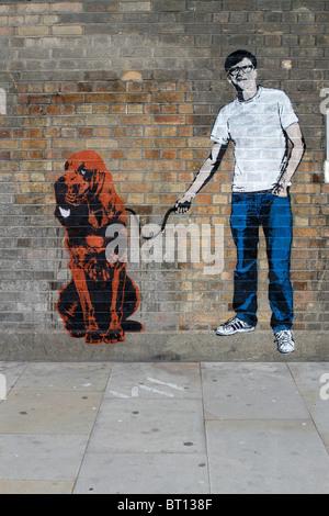 man with dog stencil graffiti banksy style, shoreditch London - Stock Photo