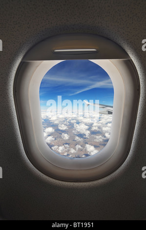cloudscape seen through an airplane window from the passenger seat - Stock Photo