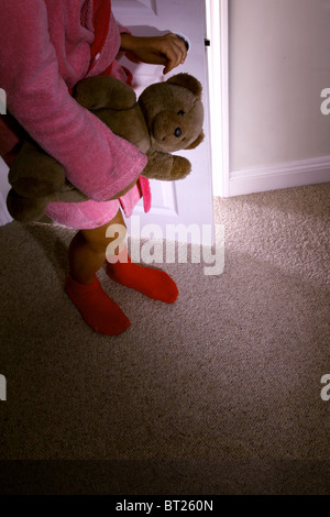 Little girl clutching a teddy bear standing behind an open door. Model and property (owned by photographer) released. - Stock Photo