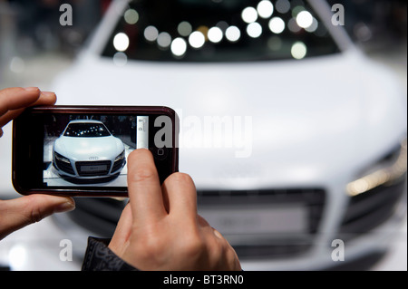 Visitor photographing Audi R8 GT at Paris Motor Show 2010 - Stock Photo