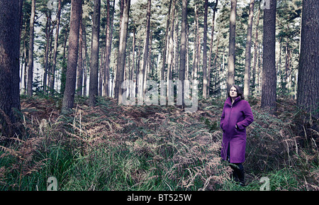 Shot of a Woman in Purple Coat in Forest - Stock Photo