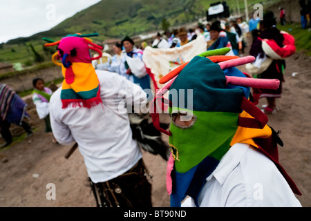 A man dancer, wearing a colorful masque, leads the procession during the Inti Raymi fiesta in Pichincha province, - Stock Photo