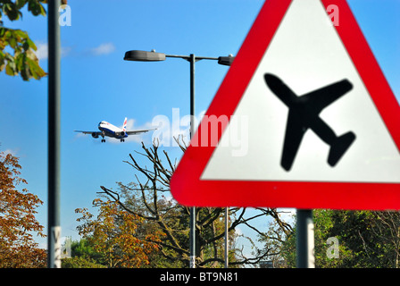 Low flying  passenger jet landing at Heathrow airport with 'low aircraft' road transport sign in foreground - Stock Photo