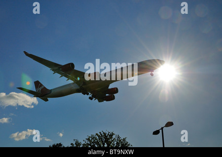 Low flying  passenger jet landing at Heathrow airport - Stock Photo