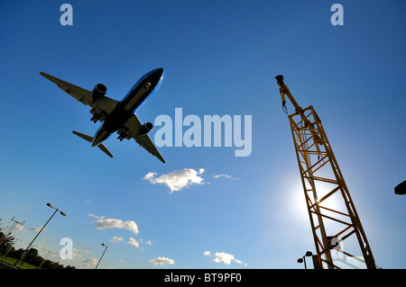 Low flying  passenger jet landing at Heathrow airport - Stock Photo
