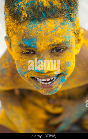 Happy young Indian boy covered in coloured powder. India - Stock Photo