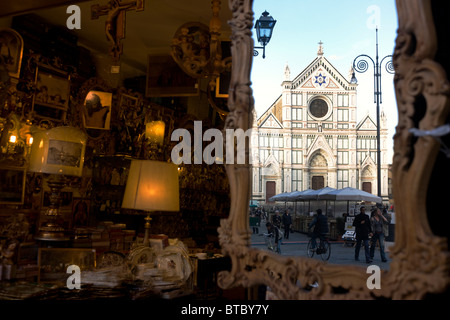 Religious icons and souvenirs with Santa Croce church reflected in mirror at end of Piazza. - Stock Photo