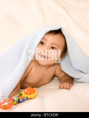 cute kid lying down on his tummy on blanket with stuck out tongue playing peek-a-boo - Stock Photo