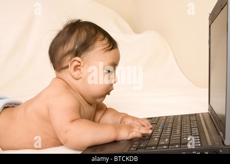 Infant Asian boy playing with laptop keyboard (profile view) - Stock Photo