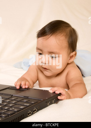 Kid playing with portable computer, surfing net, checking e-mail, playing games. That's the sign of modern time, - Stock Photo