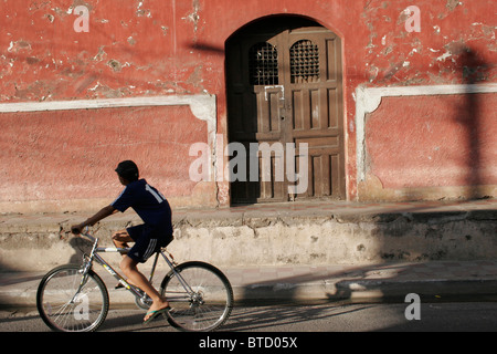 Boy on bicycle riding through street past red building in Granada, Nicaragua - Stockfoto