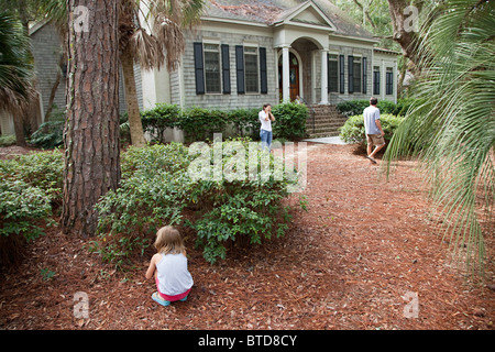 Family playing hide and seek in garden - Stock Photo