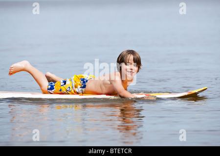 Young boy paddling on a surfboard.  Lake Winnipeg, Manitoba, Canada. - Stock Photo