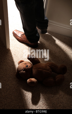 Man (feet and legs only) wearing brown shoes stepping over a teddy bear lying on the floor by an open door. - Stock Photo