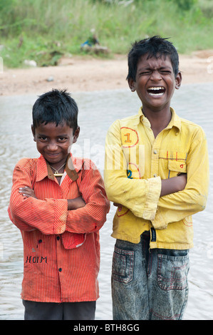 Young poor Indian boys pulling a funny faces and laughing - Stock Photo