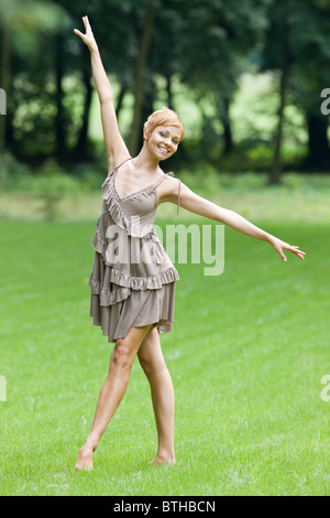 young woman dancing in park - Stock Photo