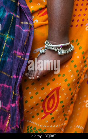 Indian babies bare foot against mothers colourful clothing - Stock Photo