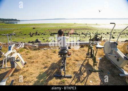 boy on exercise bike next to beach - Stock Photo