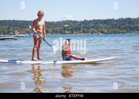 boy and girl on paddle board - Stock Photo