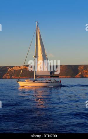 Sailboat sailing golden sunrise in blue ocean sea - Stock Photo