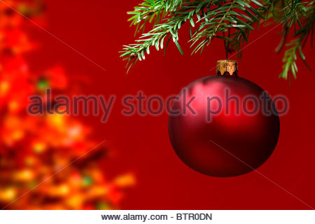 Red Christmas ornament hanging, with copy space to the left. - Stock Photo