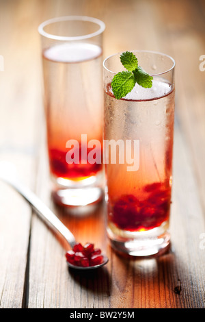 two cold pomegranate drinks or cocktails - Stock Photo
