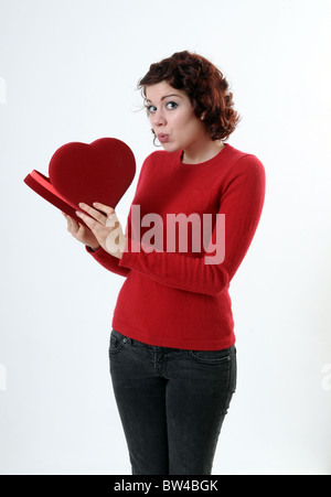 Woman peeking into a heart shaped box - Stock Photo