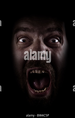 Scared face of spooky man in the dark - Stock Photo