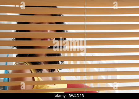 Young woman looking out of a window - Stockfoto