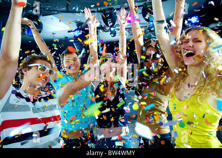 Photo of excited teenagers in confetti raising their arms expressing joy - Stock Photo