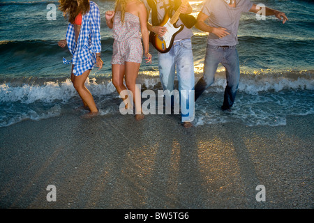 Group dance with guitar in beach tide - Stock Photo