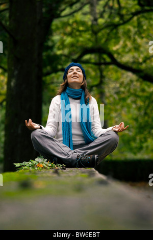Beautiful young woman in nature making meditation exercises - Stock Photo