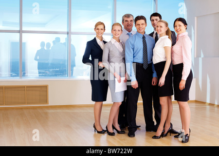 Portrait of confident business group standing next to each other and looking at camera - Stock Photo