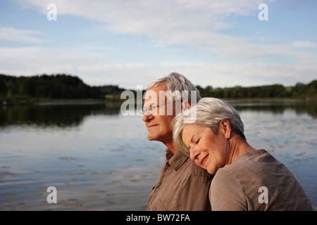 Senior woman lying head on mans shoulder - Stock Photo