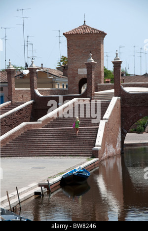 A young blonde woman walks up the stairs of Trepponti, the main sight in Comacchio, Emilia Romagna, Italy - Stock Photo