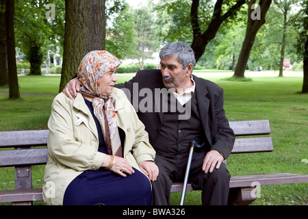 Elderly married Turkish couple on a park bench, Herne, Germany - Stock Photo