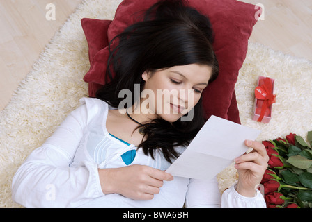 Young woman reading a love letter - Stock Photo