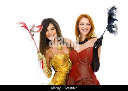 Portrait of glamorous ladies in smart dresses and with masks in hands - Stock Photo