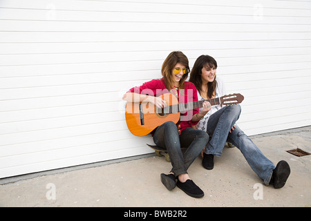 Two girls sitting on floor with guitar - Stock Photo