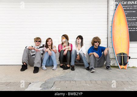 Friends sitting on floor with surfboard - Stock Photo