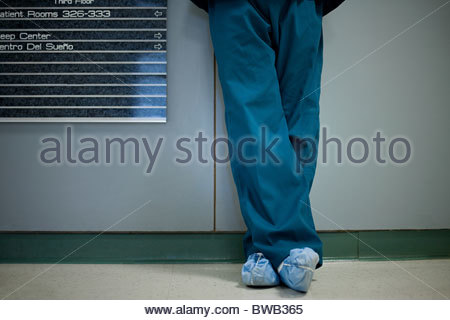 Hospital surgeon wearing shoe protectors, low section - Stock Photo