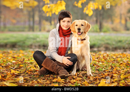 A beautiful woman and his dog (Labrador retriever) posing outside - Stock Photo